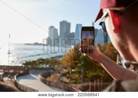 Young man taking a photo from a footbridge