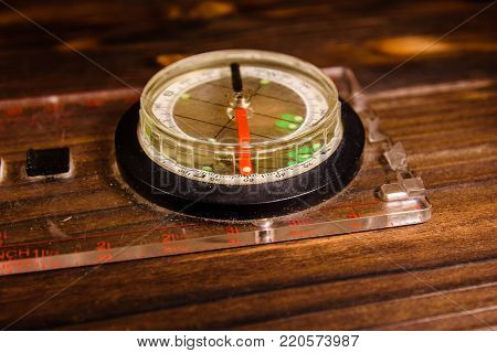 Touristic magnetic compass on a rustic wooden table