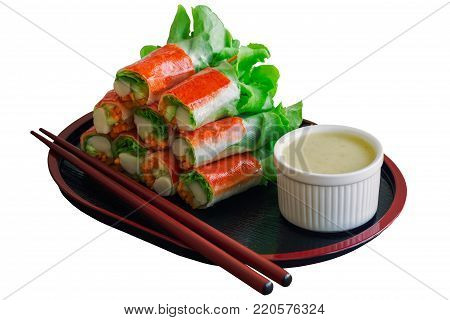 Fresh spring rolls with fresh vegetables and crab stick and wasabi mixed salad cream dressing. Salad rolls on white isolated background with clipping paths. Fusion food for appetizer or meal in Japanese style. Fresh spring rolls or salad on black plate.