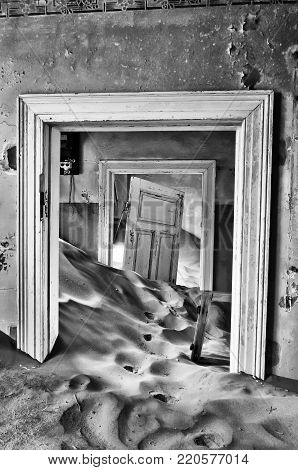 Sand taking over an historic old building at the ghost town of Kolmanskop near Luderitz, Namibia. Monochrome