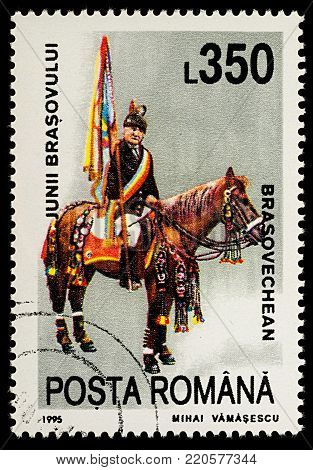 Moscow, Russia - January 04, 2018: A stamp printed in Romania, shows celebrating man with flag riding on a horse, Brasovechean, series