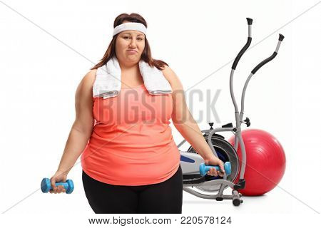 Tired overweight woman exercising with small dumbbells in front of exercise equipment isolated on white background
