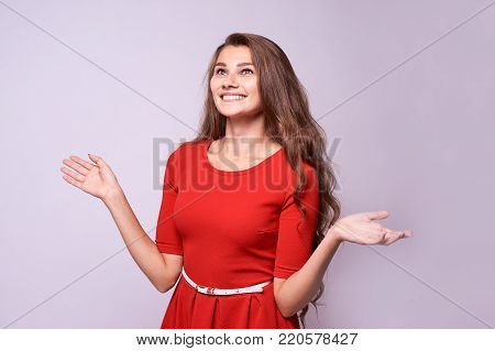 Surprised girl. Sincere joy. Red dress. Beautiful brunette.