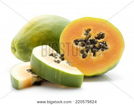 Green papaya (pawpaw, papaw) one whole one half and two slices with seeds isolated on white background