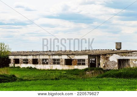 Old abandoned collapsing dilapidated agricultural building. Farm in decline.