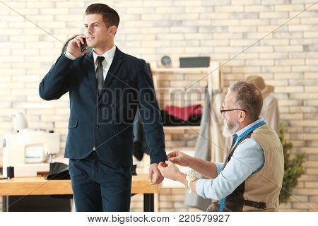Senior man tailoring formal suit for businessman in atelier poster