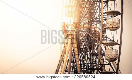 Close up view of the gondolas suspended from the rim of a ferris wheel lit by the warm glow of the sun at an amusement park with copy space