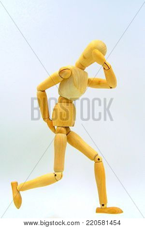Wooden mannequin figure expressing caught by diarrhea and feeling a shame. Selective coloring.