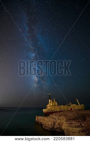 Night sky with the Milky Way and cargoship aground near sea shore