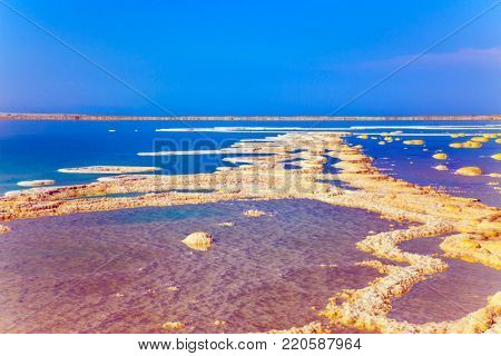 Therapeutic Dead Sea, Israel. The evaporated salt is precipitated by picturesque stripes in shallow water. The concept of medical and ecological tourism