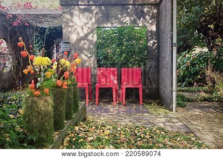 Appeltern, Netherlands, September 29, 2017: Characteristic patio with three red chairs as opportunity to sit