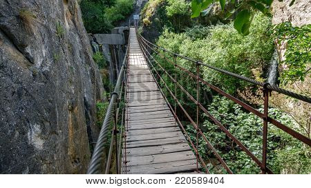 Wide angle of Iron and wooden suspension bridge in canyon between high vertical rocks