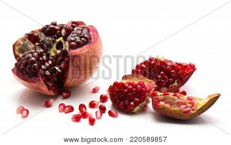 Pomegranate pieces with revealed grains isolated on white background one split open