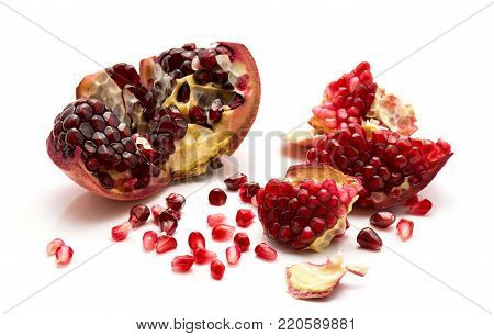 Split open pomegranate with revealed grains isolated on white background