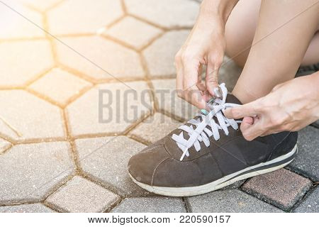Woman getting ready to run and tying running shoes