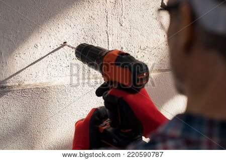 Close up construction workerâ??s hand using electric drill making hole in wall. Detail of bricklayer hands holding drilling machine and working on building site. Builder drilling a hole in the wall.