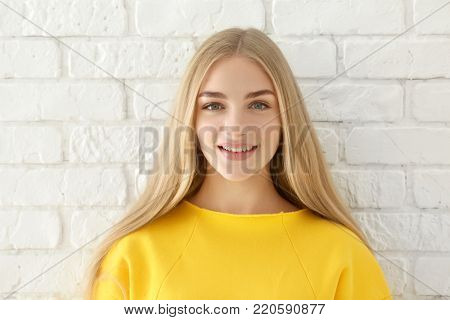 Smiling woman in yellow sweatshirt on brick wall background