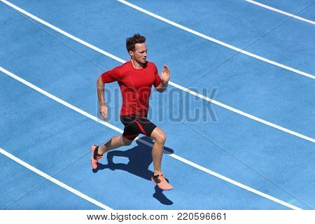 Sprinter man running on blue tracks lanes in track and field stadium in high speed top view. Male athlete runner in intense sprint training. Run sport concept
