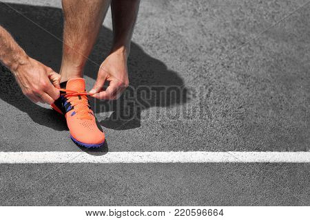 Runner man ready to start running on asphalt street tying up running shoes laces on grey background. Copy space for text with starting line.