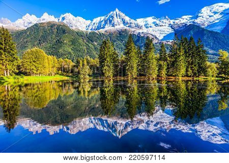 Mountain resort of Chamonix. Stunning reflections of snowy peaks in the lake water. Fantastic sunset in the autumnal Alps. Concept of active and ecotourism