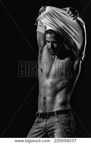 Handsome man or unshaven macho, bodybuilder, with stylish blond hair, haircut, undressing white tshirt, showing sexy, muscular torso, six packs and abs, male striptease on black background