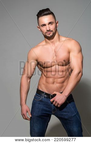 Sport and workout. Dieting and fitness. Athletic bodybuilder man on grey background. Man with muscular body and torso. Coach sportsman with bare chest in jeans.