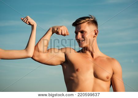 Man with strong hand biceps, triceps smile at female hand on blue sky. Contrast, competition, conflict concept. Masculinity and femininity. Sport, fitness, strength
