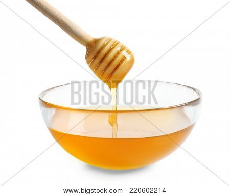 Honey pouring from wooden honey dipper into glass bowl on white background