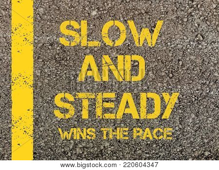 Slow and Steady, written on road asphalt