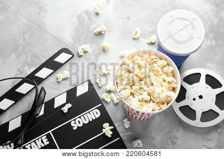 Tasty popcorn, movie reel and clapboard on grey background