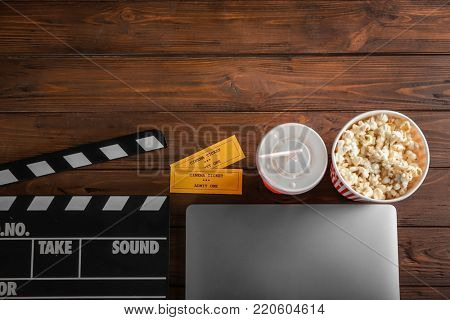 Composition with laptop, movie tickets and clapboard on wooden background, top view