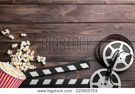Tasty popcorn, movie reel and clapboard on wooden background