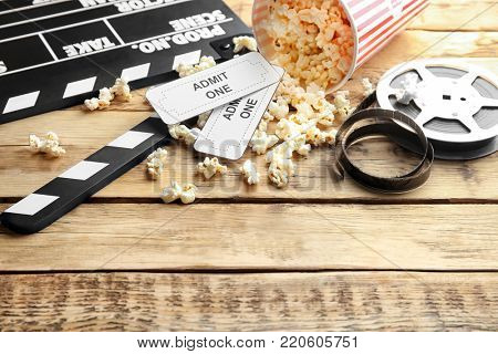 Tasty popcorn, tickets, clapboard and movie reel on wooden background