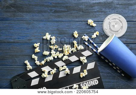 Tasty popcorn and clapboard on wooden background