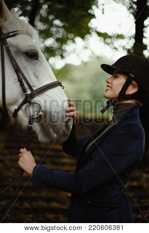 Beautiful horsewoman in blue jacket strokes white horse