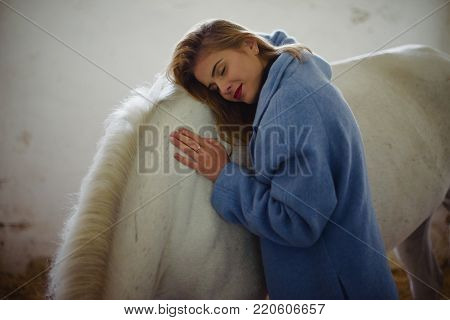 Woman with dark red lips hugs white horse