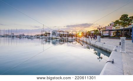 Beautiful Marina in Limassol city Cyprus. A modern, high end life and newly developed port with docked yachts, restaurants, shops, a landmark for waterfront promenade. View of the commercial area at sunset.
