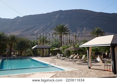Swimming Pool In A Beautiful Residence With Palm Trees And A Mountainous Background