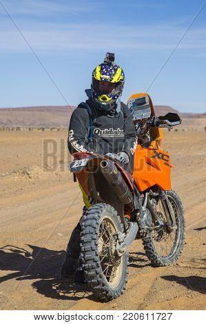Merzouga, Morocco - February 26 2016: Person Next To A Motobike With Action Cam Fixed On His Helmet