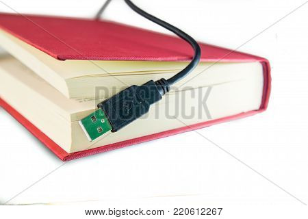 USB calbe coming out of a book with red covers. Ebook concept, audio book concept or information technology. Isolated on white.