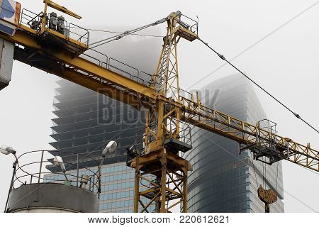a crane at a construction site in foggy weather, on the background of the unfinished skyscrapers