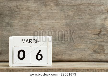 White block calendar present date 6 and month March on wood background