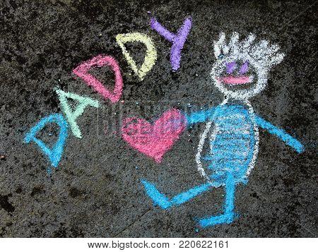 chalk drawing on asphalt: Cute father portrait and word DADDY