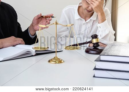 Close up of gavel, Male lawyer or judge Consult with client and working with Law book, report the case on table in modern office, Law and justice concept.