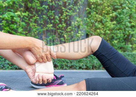 Young woman runner ankle being applied bandage by man in park. injury ankle.