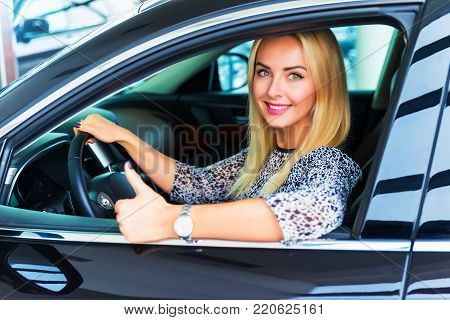 Happy smiling blonde woman driver showing thumbs up in her new luxury car