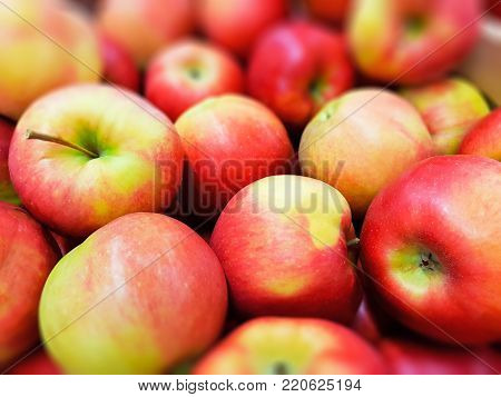 Macro view of the heap of fresh red apples at the food market, supermarket or grocery store with selective focus effect