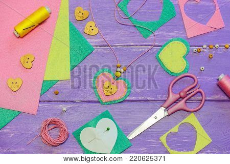 Heart shaped pendant necklace. Valentines day necklace made of colored felt, beads and a wooden button. Craft supplies on a wooden background. Gift for mother. Kids arts and crafts activity
