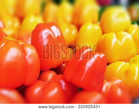Macro view of the heap of fresh red and yellow sweet peppers at the food market, supermarket or grocery store with selective focus effect