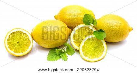 Composition of whole lemons and its slices on fresh green melissa leaves isolated on white background